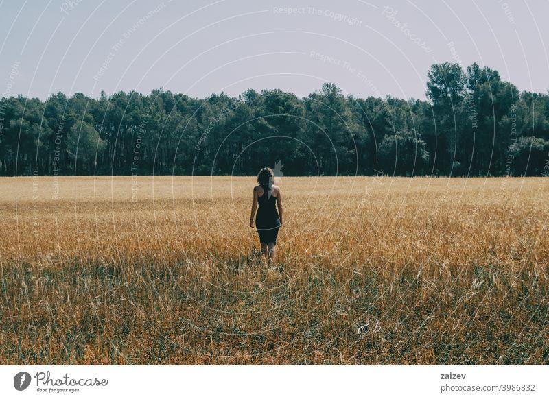 Mädchen geht durch ein schönes gelbes Feld horizontal Frieden Ruhe produzieren Wachstum golden wachsen Land Licht außerhalb Farbbild idyllisch panoramisch Weg