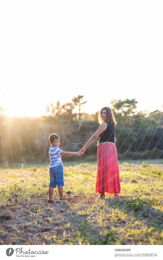 Frau und Kind halten sich auf einer Wiese an den Händen Herbst schön Kaukasier heiter Kindheit Tochter Genuss fallen Familie Feld Wald grün Fröhlichkeit Glück