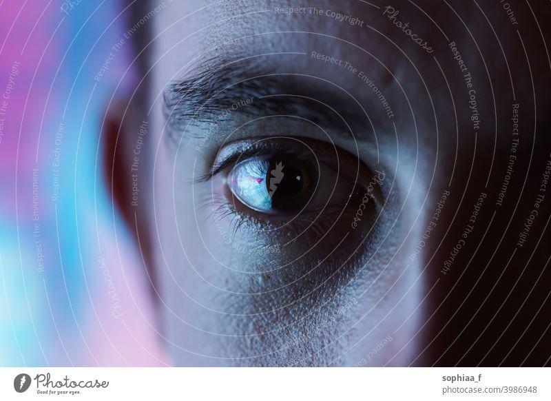 Ausdrucksstarker Blick - Nahaufnahme eines Auges mit unscharfem blauem und rosa Neonlicht-Hintergrund und hohem Kontrast Disco-Licht hoher Kontrast Mann Farbe