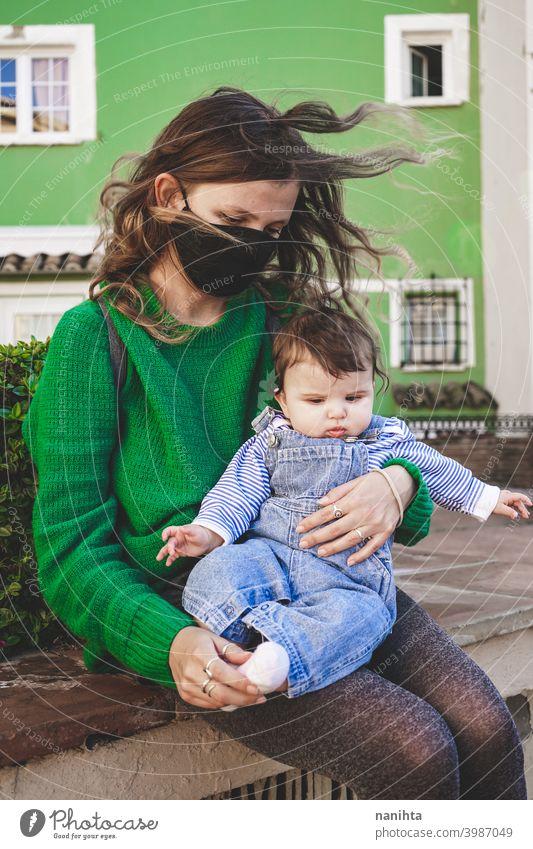 Bild in Grüntönen einer jungen alleinerziehenden Mutter mit ihrem Baby während der Covid-Pandemie COVID Coronavirus Familie Mutterschaft Mama Mundschutz