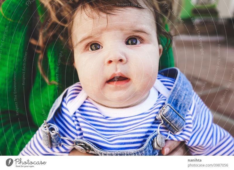 Liebliches junges Baby in den Armen seiner Mutter Familie Mutterschaft Mama grün urban lange Haare Zeit Trave Feiertage Jeanshose lässig anhaben junge Mutter
