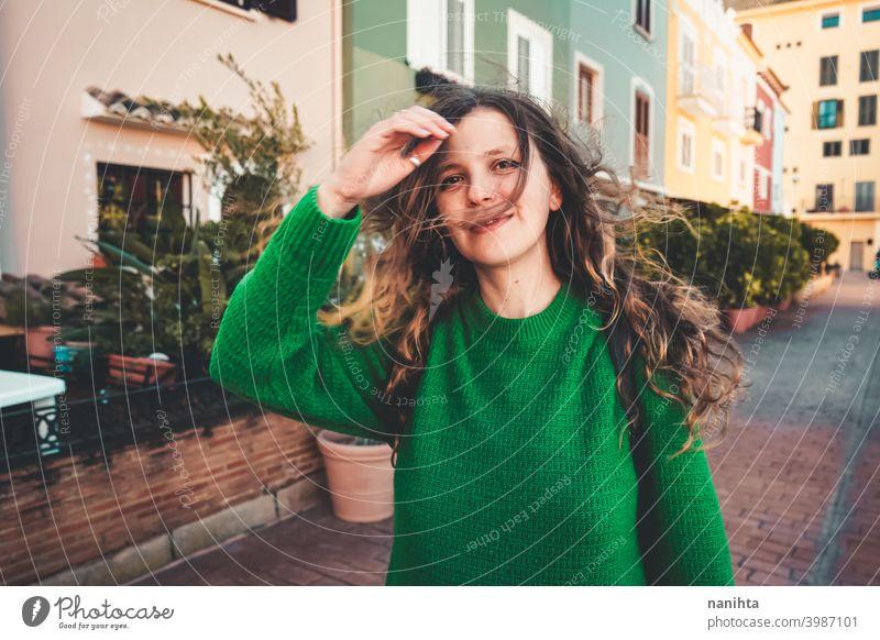 Junge Frau trägt grünen Oversize-Pullover und genießt einen windigen Tag in einer bunten Stadt reisen Porträt Lifestyle Model Europa Europäer blond im Freien