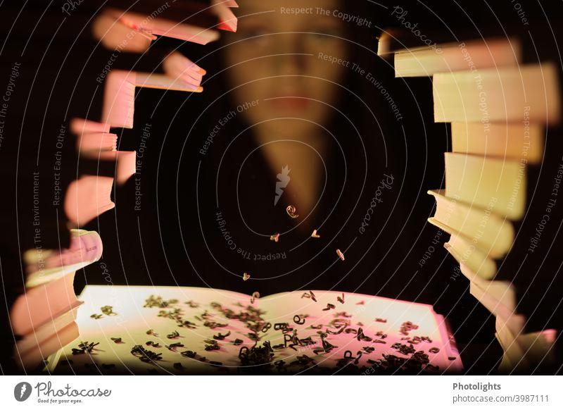 Frau hinter Bücherstapel sieht fliegenden Buchstaben zu bücher Literatur lesen zaubern Zauberei Lesestoff Buchseite Bibliothek Wissen Bildung Schule Stapel