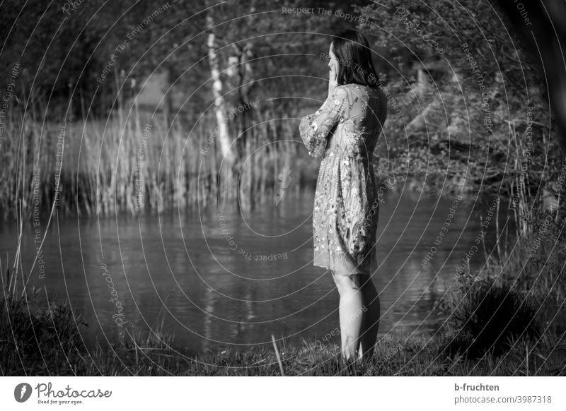 Frau im Sommerkleid steht am Bach nachdenken Schwarzweißfoto Gewässer Denken Gesicht Blick Gedanke Trauer ruhig Hand Traurigkeit wartend Angst Einsamkeit