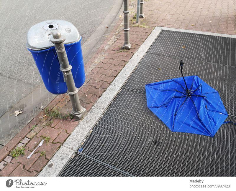 Blauer Müllheime neben und blauer Regenschirm auf dem Lüftungsgitter einer U-Bahn Station an der Senckenberganlage im Westend von Frankfurt am Main in Hessen