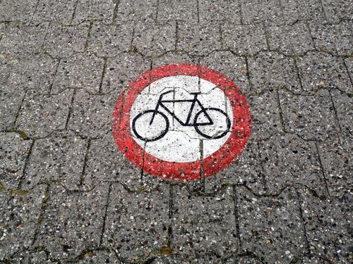 Ein rundes Verkehrszeichen auf das Verbundpflaster gemalt verbietet die Durchfahrt für Fahrräder auf dem Deich am Hafen von Neuharlingersiel bei Esens in Ostfriesland im Kreis Wittmund in Niedersachsen
