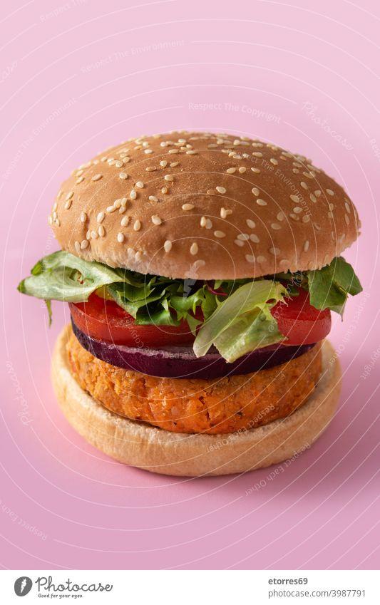Kichererbsen-Burger mit Kopfsalat, Tomate und Zwiebel auf rosa Hintergrund alternativ Brot Diät Lebensmittel frisch Gesundheit Bestandteil Feldsalat Mittagessen