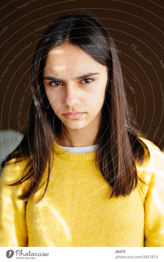 Porträt eines unglücklichen und unzufriedenen Teenager-Mädchens mit einem gelben Pullover wütend verärgert ernst mürrisch gereizt Stress frustriert Blick