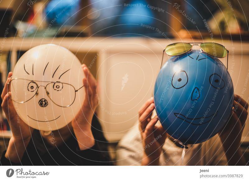 Mit lustigen Gesichtern bemalte Luftballons vor den Köpfen zweier Kinder | Aufgemalte Augen, Nase, Mund, Haare und aufgesetzte Brille | Hände halten den Luftballon fest