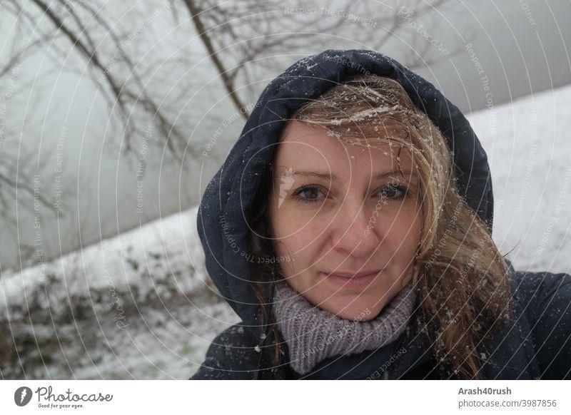 Junge Frau im Schneefall mit Kapuze (Selbstportrait) sportlich Bewegung Erholung kalt Winter schneeflocken Augen Nase Mund lange Haare Blond blau Jacke