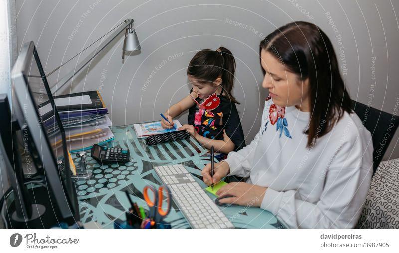 Frau bei Telearbeit mit ihrer Tochter beim Zeichnen Vereinbarkeit von Familienarbeit Heimarbeit Coronavirus Quarantäne Schreiben einer Notiz Computer Seuche