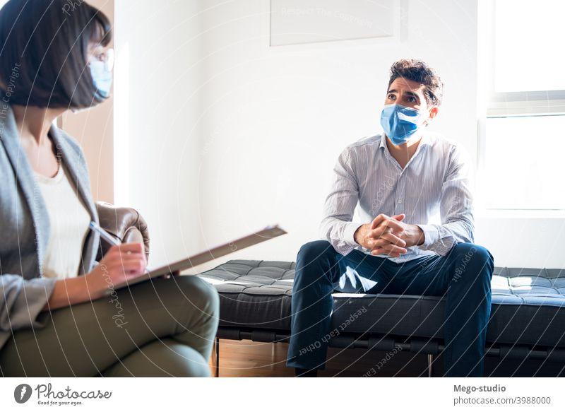 Psychologe im Gespräch mit dem Patienten während einer Therapiesitzung. Psychologin professionell Notizen geduldig mental Gesundheit Gesichtsmaske Therapeut