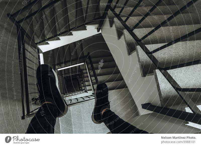 Hohe Ansicht der Treppe und der Männerschuhe von oben. Gebäude Quadrat schwarz Selfie Lifestyle Schatten Tiefe Schwindelgefühl Architektur Innenaufnahme