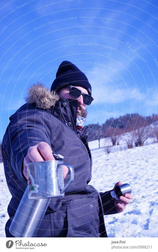 Das Tee-einschenk Model, Junger Mann mit Sonnenbrille im Schnee, Teekanne und Becher in der Hand. Lifestyle Freizeit & Hobby im Freien Wandertag Landschaft