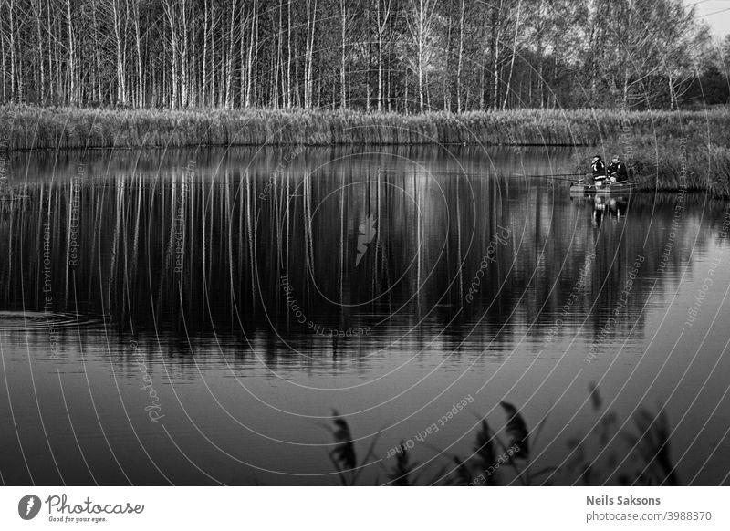 zwei Fischer in einem Boot mit Spiegelung in einem stillen Flusswasser bei Dämmerung auf Herbstlandschaft. allein Anker schön Lettland Liegeplatz Birke