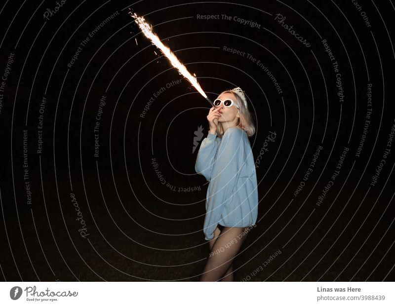 Es ist Freitagabend und mir geht es gut. Die Party ist hier auf der Westseite. Das blonde Mädchen bläst Feuer und hat eine gute Zeit. Feuerwerk Stichflamme