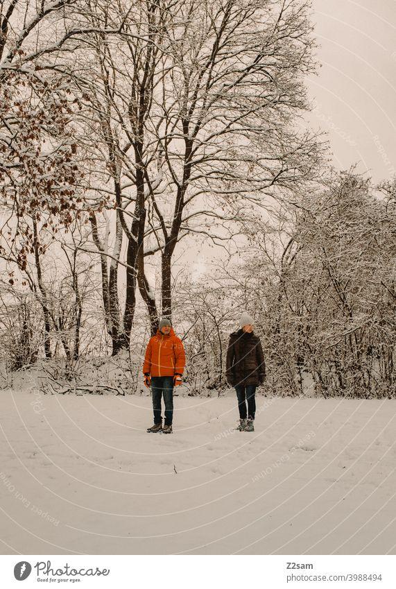 Renterpaar in Winterlandschaft spaziergang winter winterlandschaft schnee kälte bäume sträucher frau mann rente rentner entspannen erholung stehen