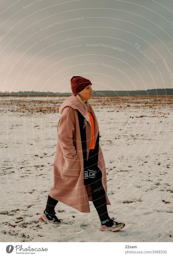 Modisch gekleidete Junge Frau geht  spazieren winterwonderland frau junge frau mantel spaziergang schnee sonne licht natur landschaft schal mütze lange haare