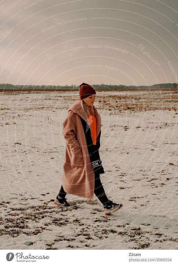 Modisch gekleidete Junge Frau geht bei leichtem Schneefall spazieren schneien winterwonderland frau junge frau mantel spaziergang schnee sonne licht natur