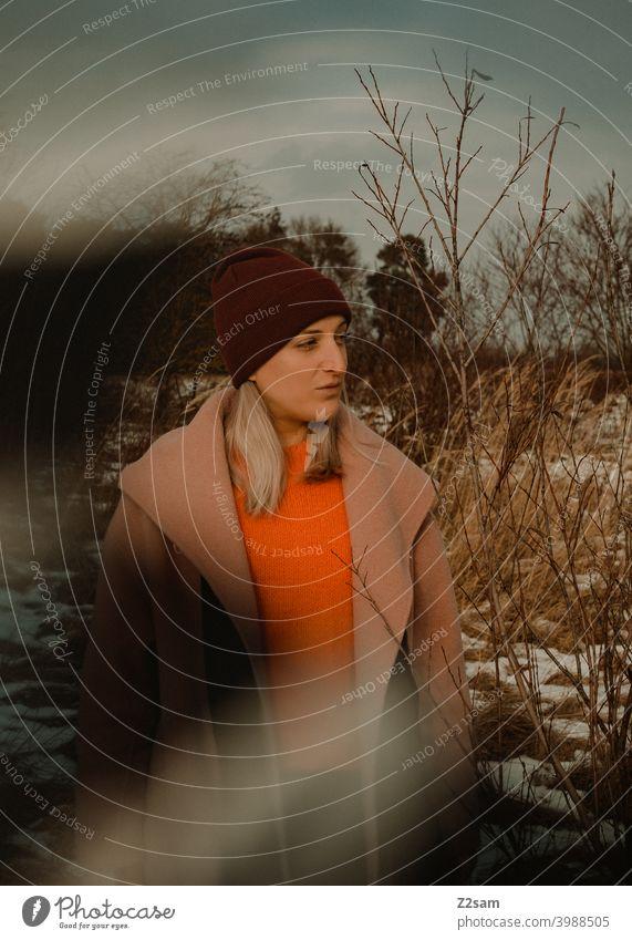Portrait einer modisch gekleideten Frau in Winterlandschaft winterwonderland frau junge frau mantel spaziergang schnee sonne licht natur schal mütze lange haare