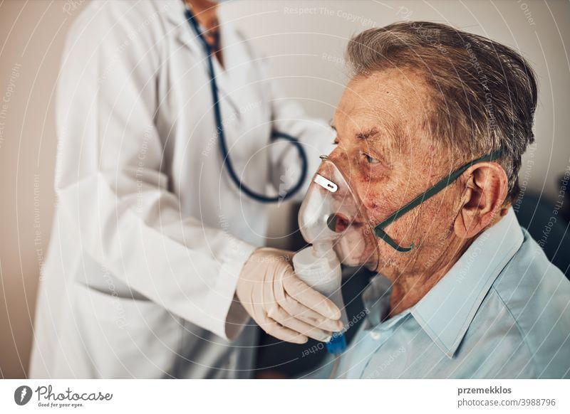 Arzt, der einem älteren Mann, der an einer Lungenkrankheit leidet, ein Medikament während der Inhalation verabreicht. Behandlung von Covid-19 oder Coronavirus
