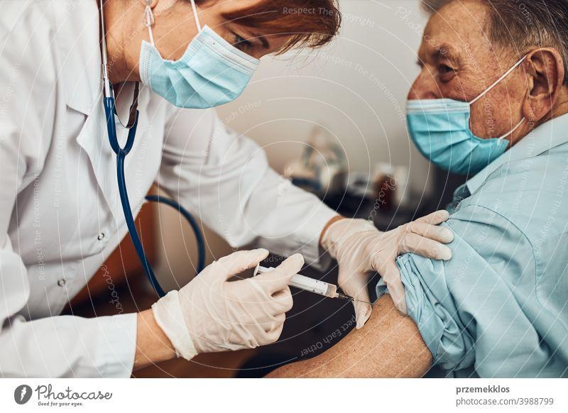 Der Arzt hält die Spritze mit dem Impfstoff und führt die Injektion bei einem älteren Patienten durch. Impfstoff gegen Covid-19 oder Coronavirus geduldig Person