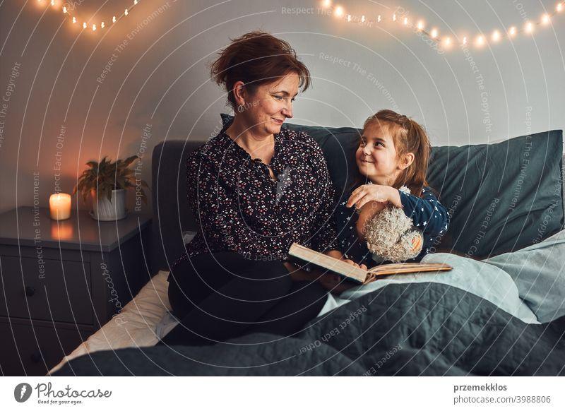 Mutter lesen Buch ihre Tochter im Bett vor dem Schlafengehen. Gutenachtgeschichten für Kind Nacht Schlafenszeit Familie heimwärts Literatur Frau Schlafzimmer