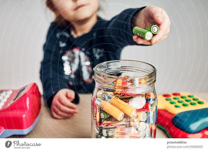 Kleines Mädchen, das verbrauchte Batterien in ein Gefäß zum Recyceln legt. Kind trennt Abfall Recycling Person umgebungsbedingt konzeptionell Verantwortung