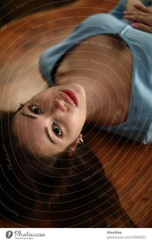 Überkopf- Porträt einer jungen, brünetten Frau mit einem hellblauen Oberteil die auf einem Holztisch liegt und nach oben in die Kamera schaut Junge Frau hübsch