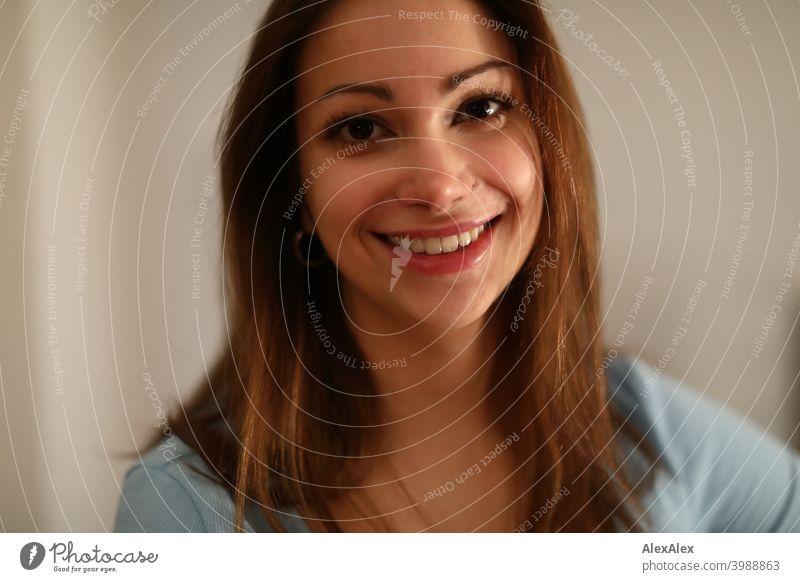 Portrait einer jungen, brünetten, breit lächelnden Frau mit einem hellblauen Top in einem hellen Raum junge Frau schön Freude langhaarig anmutig lachen Grübchen