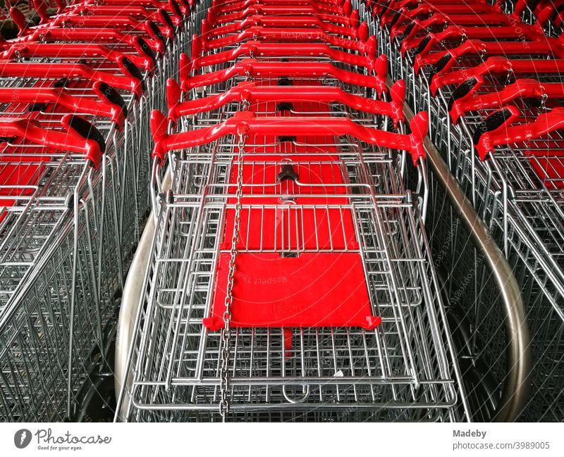 Aufgereihte Einkaufswagen aus glänzendem Draht mit rotem Plastik vor einem neuen Supermarkt in Bielefeld im Teutoburger Wald in Ostwestfalen-Lippe Shopping