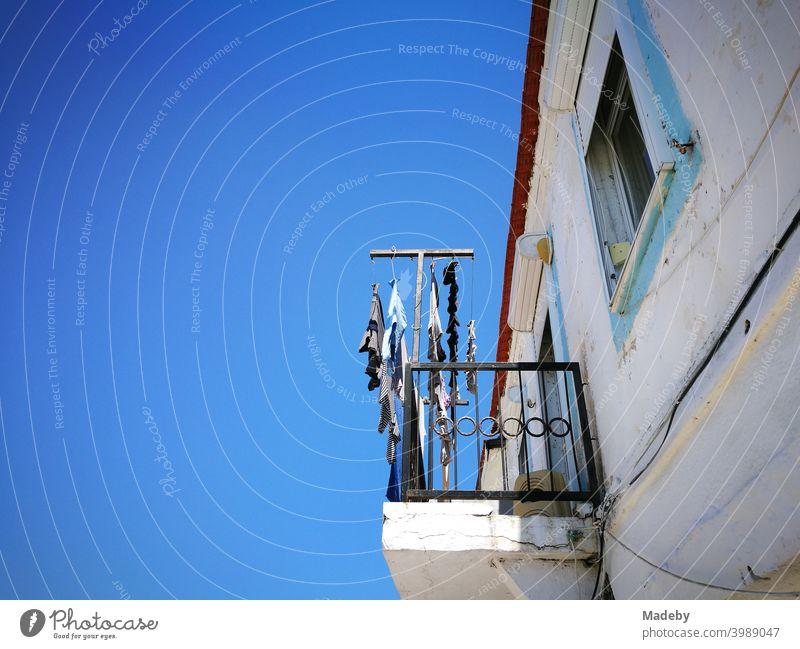 Altes weißes Haus mit Balkon und Wäscheleine vor strahlend blauem Himmel im Sommer bei Sonnenschein in Alacati bei Izmir am Ägäischen Meer in der Türkei