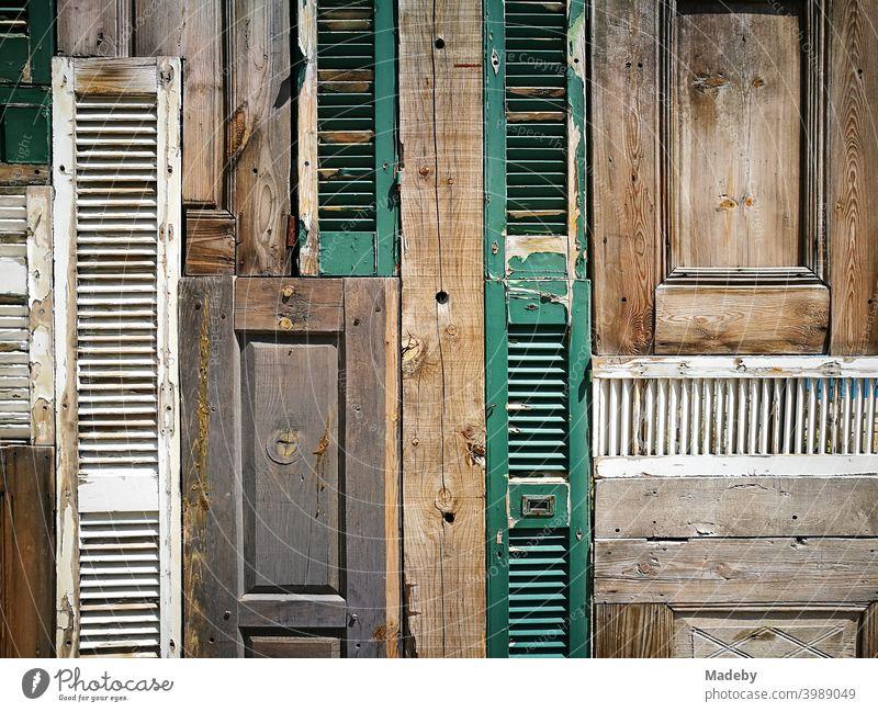 Dekorative Wand aus alten Holztüren und Fensterläden in einer Bar unter freiem Himmel in der Altstadt von Alacati am Mittelmeer bei Izmir in der Türkei