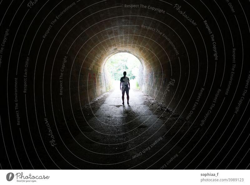 Escape the Darkness - Silhouette eines Mannes, der im Licht am Ende des Tunnels steht Stollen Einsamkeit Dunkelheit Depression Ausfahrt Zukunft Freiheit