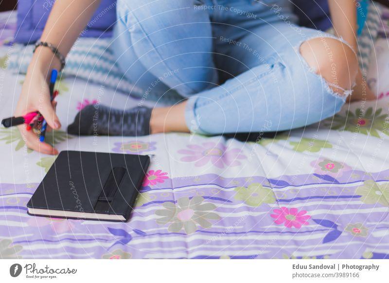 Junge Frau schreibt in ihr Tagebuch. Büro Buch Schüler Brief Papier Männer bei der Arbeit Job Notizblock Plan Beteiligung Nahaufnahme Person weiß Page