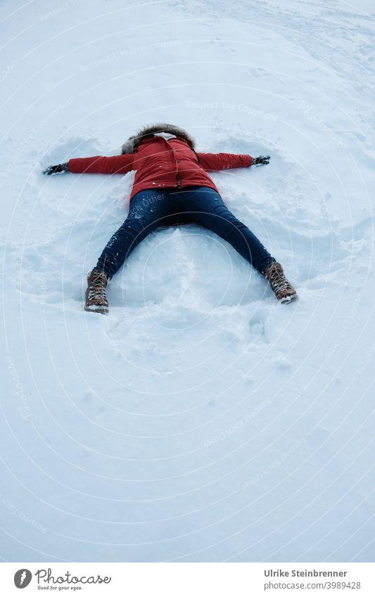 Frau in rotem Anorak macht einen Schneeengel Winter Spaß Neuschnee Winterspaß Engel Engelsflügel Abdruck Wiese Schneedecke weiß kalt Kapuze Wetter Beine Jeans