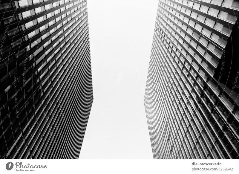 Blick in den Himmel zwischen zwei Hochhäusern Moderne Architektur Draußen Farblos Fluchtlinien Hochhaus Gebäude Kontrastreich Stadt Symmetrie Wolkenkratzer grau