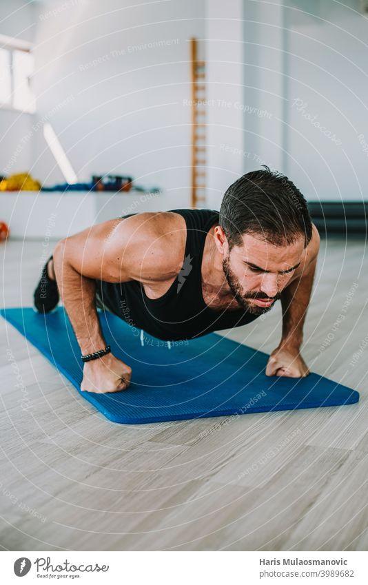 Mann trainiert im Fitnessstudio, macht Liegestütze, Fitnesstraining, gesunder Lebensstil aktiv Erwachsener Waffen Athlet sportlich Körper Bodybuilding Kaukasier