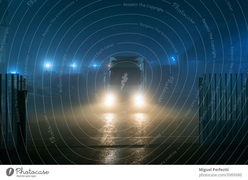Lkw verlässt eine Fabrik bei Nacht an einem sehr nebligen Tag mit schlechter Sicht. Lastwagen Nebel Lichter Dunkelheit Vorderansicht Gate Transport Verkehr groß