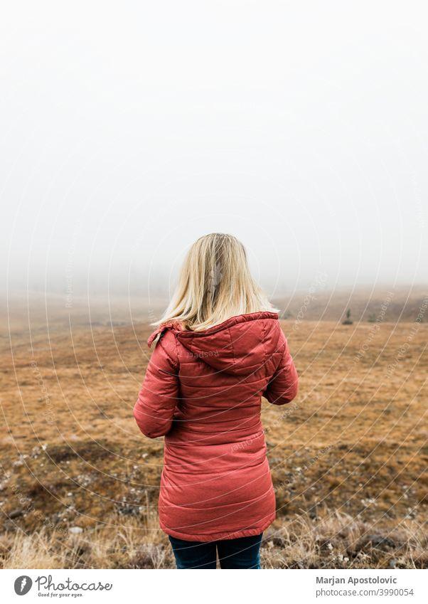 Junge Frau erkundet die Natur an einem nebligen Wintermorgen Abenteuer Herbst Cloud kalt Landschaft Fundstück Erkundung erkunden Entdecker Feld Nebel Freiheit