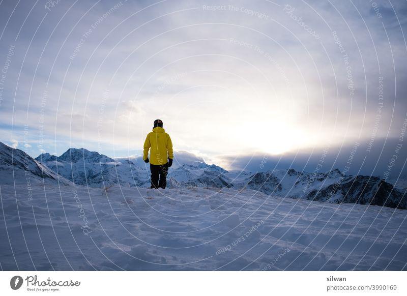 Talsicht am Abend Abendrot bergwelt Felsen Schweiz sonneuntergang Wolkenhimmel Person gelb Schnee Eis gefroren Influencer Snowboarding diffuses licht