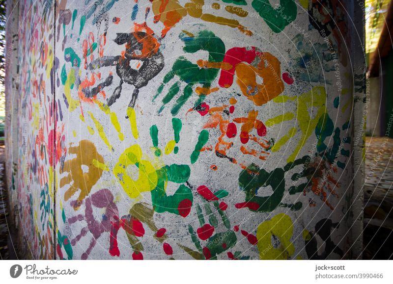 Hand in Hand gestaltete Wand Straßenkunst Abdruck viele Kreativität Teamwork Partizipation Farbenspiel mehrfarbig abstrakt Einigkeit Silhouette