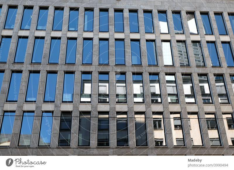 Spiegelnde blaue Fenster in grauem Beton eines modernen Bürogebäude im Sommer bei Sonnenschein in der City von Frankfurt am Main in Hessen Architektur Fassade