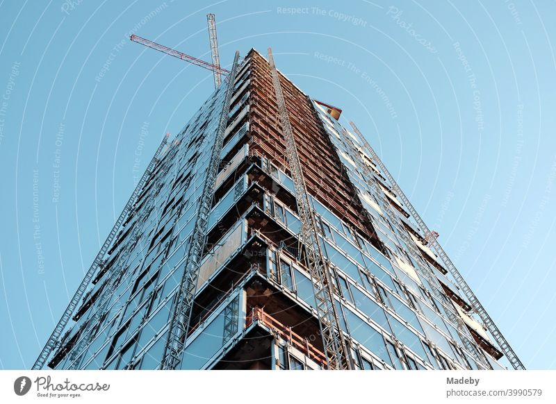 Rohbau eines modernen Hochhaus mit Luxusapartment mit zwei Baukränen vor hellblauem Himmel im Westend von Frankfurt am Main in Hessen Immobilie Wolkenkratzer