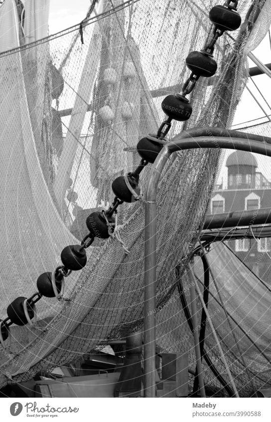 Fischernetze eines alten Fischkutter im Hafen von Neuharlingersiel an der Nordseeküste bei Esens im Landkreis Wittmund in Niedersachsen, fotografiert in klassischem Schwarzweiß