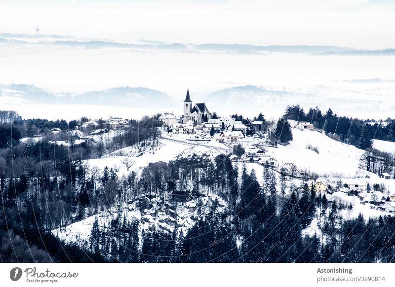 kleiner, eingeschneiter Ort in einer Hügellandschaft Allerheiligen im Mühlkreis Landschaft Natur Dorf Kirche Kirchturm Österreich Mühlviertel Winter Schnee
