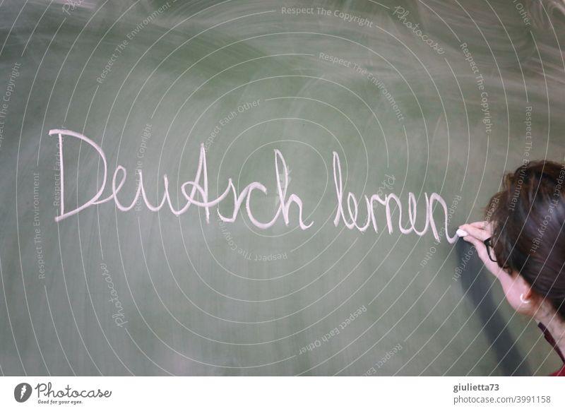Deutsch lernen - Junge Lehrerin schreibt mit Kreide an die Tafel, Unterricht Zukunftsorientiert Eingliederung eingliedern Zusammenleben