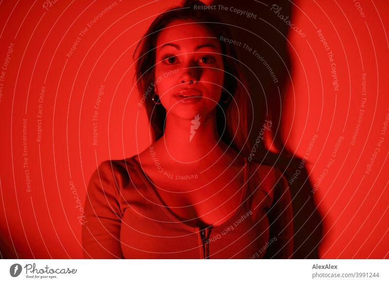 Porträt einer jungen Frau in einem Raum mit rotem Licht - das ganze Bild ist rot Junge Frau hübsch brünett langhaarig schlank feminin Teenager 18-25 Jahre