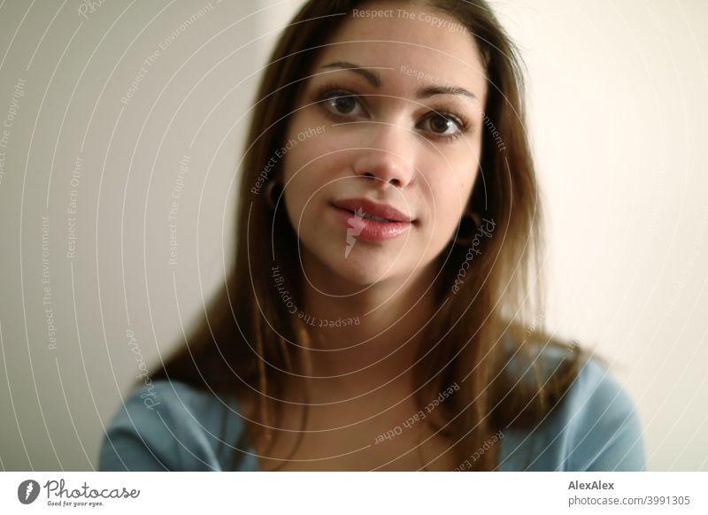 Porträt einer jungen, brünetten Frau mit einem hellblauen Oberteil in einem hellen Raum Junge Frau hübsch langhaarig schlank feminin jugendlich 18-25 Jahre