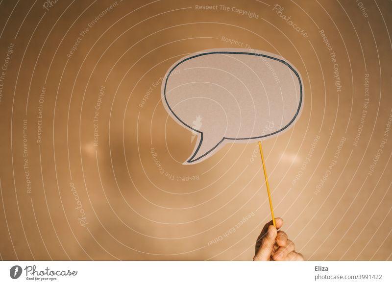 Hand hält eine leere Sprechblase vor braunem Hintergrund Kommunikation Textfreiraum copyspace Kommunizieren Sagen Meinung Mitteilung nichts